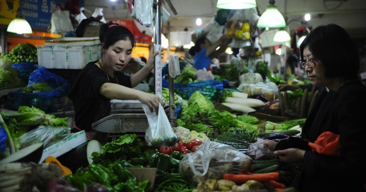 Shoppers purchase vegetables at a market in Shanghai on May 23, 2012.</p>