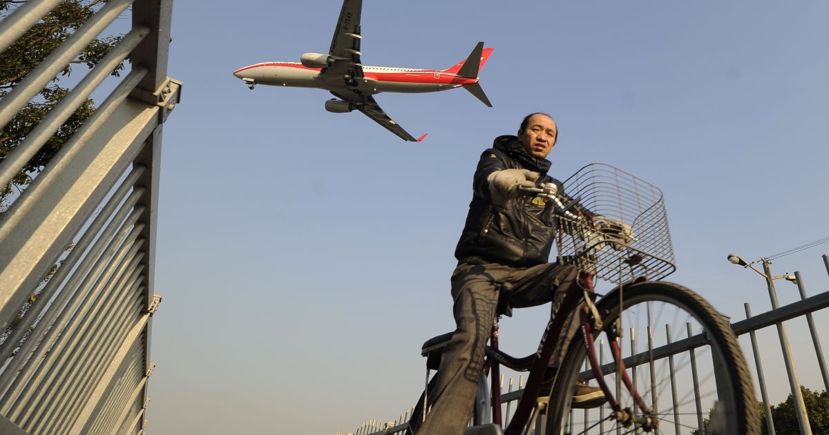 A man cycles as an airliner flies over head into Hongqiao International airport in Shanghai on Jan 5.</p>