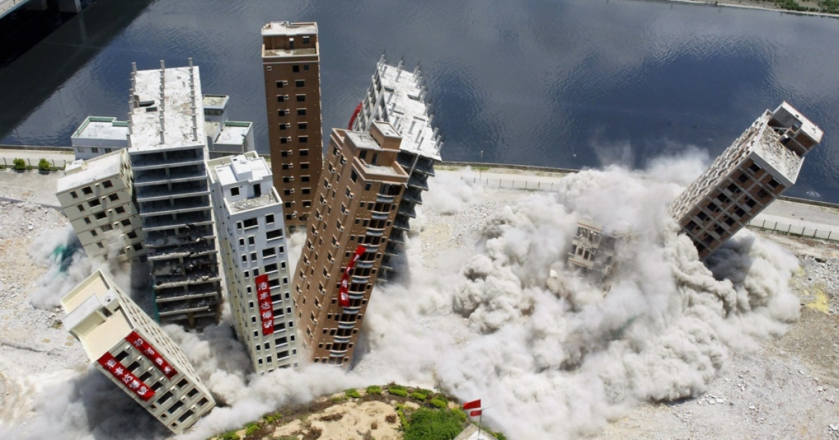 Buildings topple from a controlled-explosion set off during their demolition in the Huanggang district of Shenzhen, May 22, 2005.</p>