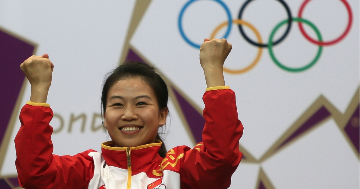 Gold medalist China's Yi Siling reacts on the podium after the 10m air rifle women's final at the London 2012 Olympic Games at the Royal Artillery Barracks in London on July 28, 2012.</p>
