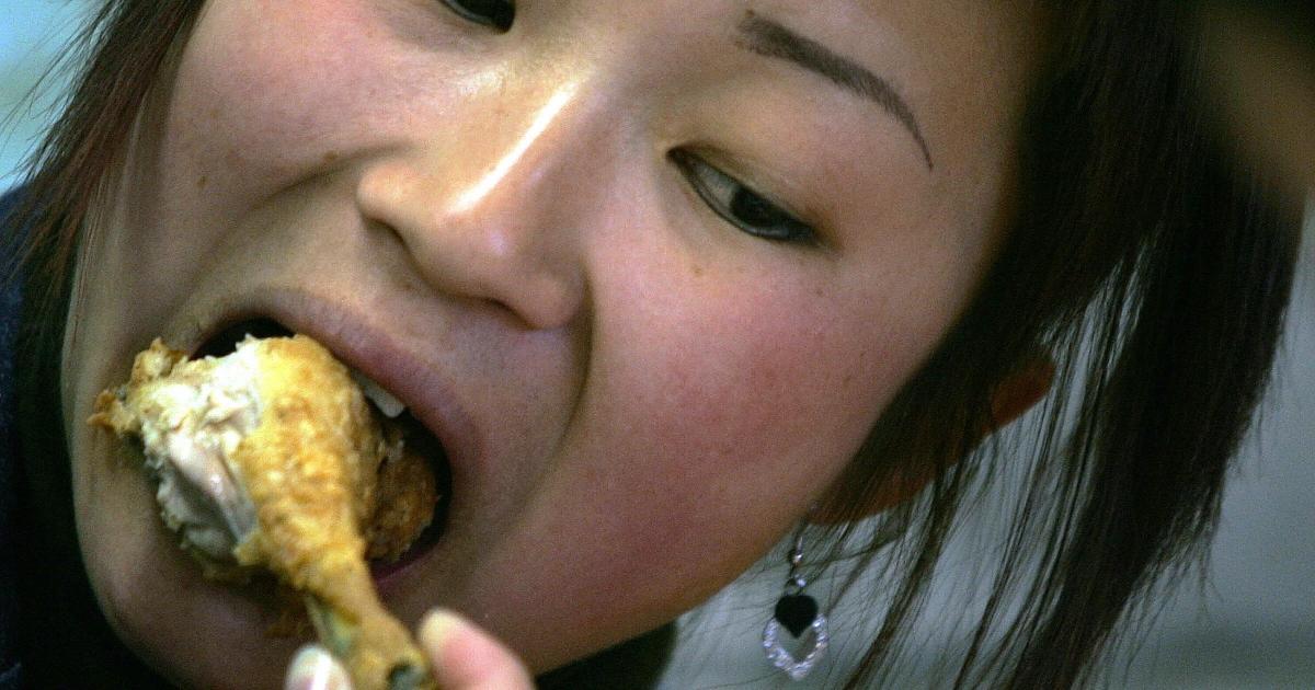 A woman eats a chicken leg at a Kentucky Fried Chicken (KFC) outlet in Beijing.</p>