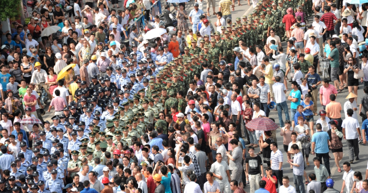 A line of paramilitary police makes its way through protesters outside the local government offices in Qidong in the eastern China province of Jiangsu on July 28, 2012. Thousands of demonstrators protested against alleged pollution from a paper factory in this easten China city and clashed with police after they seized bottles of liquor and wine from the offices along with cartons of cigarettes, items which Chinese officials frequently receive as bribes.</p>