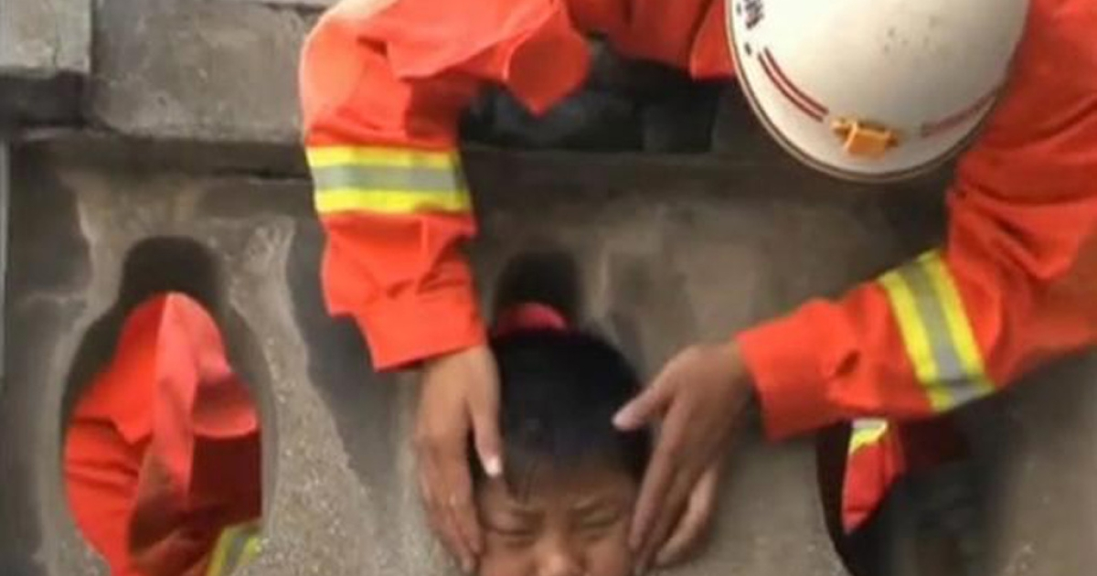Firefighters in China work to free a boy's head from a stone guardrail in Hezhang County.</p>
