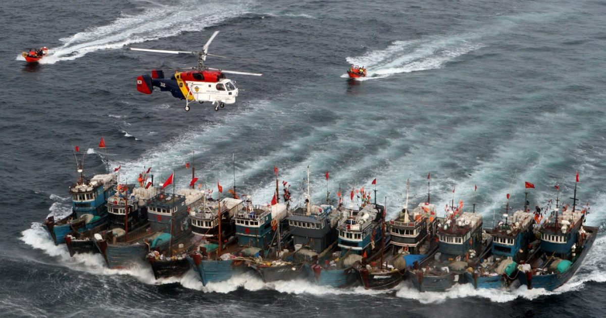 A picture taken on November 16, 2011 from a South Korean helicopter shows Chinese boats banded together with ropes, chased by a coastguard helicopter and rubber boats pacted with commandoes, after alleged illegal fishing in South Korean waters in the Yellow Sea.</p>