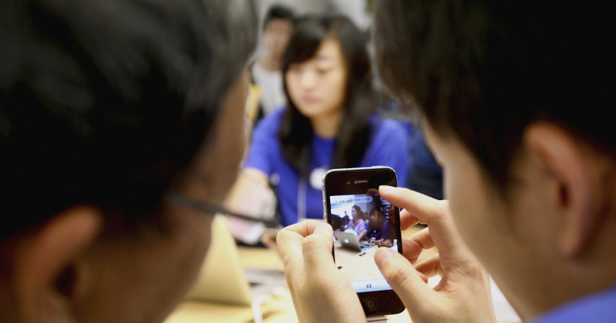 An Apple store employee introduces the iPhone 4 to a customer in Beijing, China.</p>