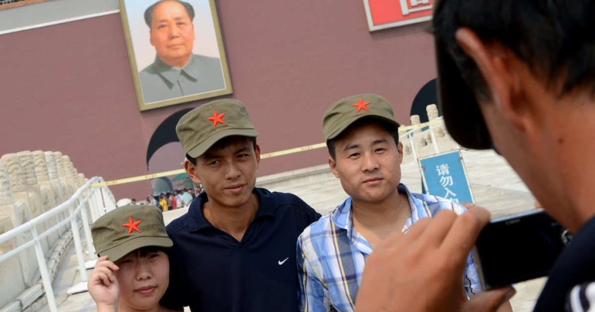 Tourists pose for a photo in front of a portrait of former Chinese leader Mao Zedong in Tiananmen Square.</p>