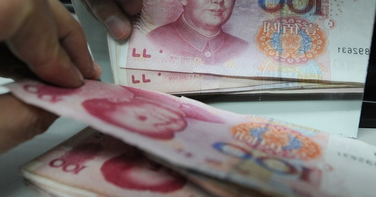 A Chinese bank worker counts a stack of 100-yuan notes at a bank in Hefei, east China's Anhui province on February 27, 2011.</p>