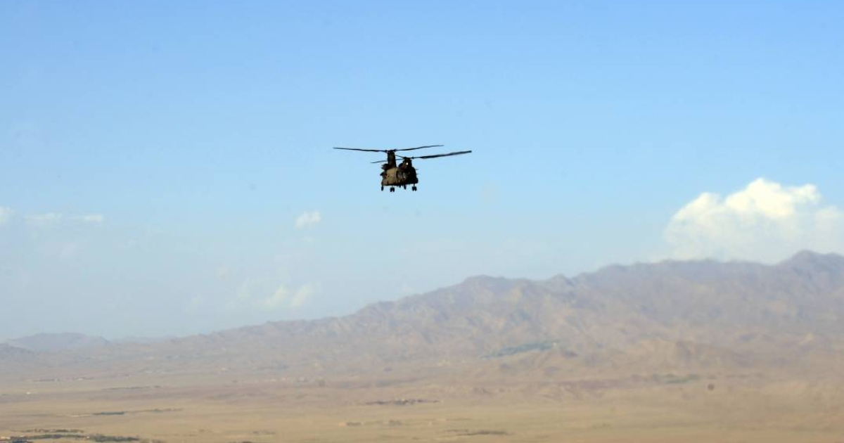 A U.S. Chinook helicopter flies over a valley in Afghanistan. An Afghan official says the Taliban laid an elaborate trap for the Chinook they shot down on Friday, killing 38 troops including 30 Americans.</p>