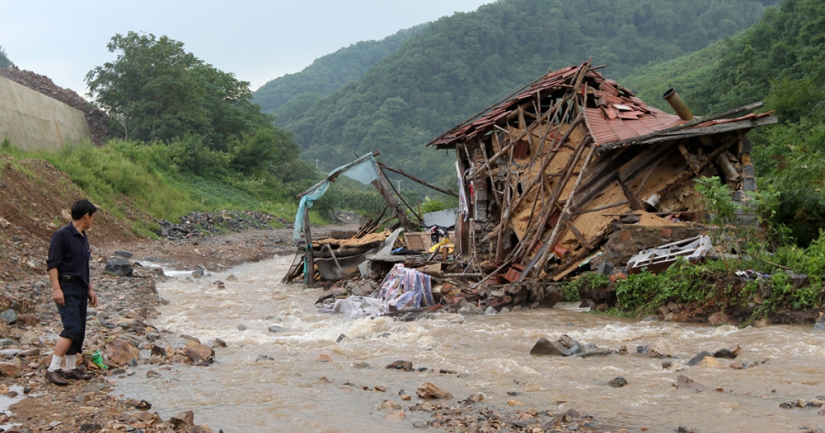 A villager looks at a destroyed home after a flash flood swept through Kuandian, near the China-North Korea border in northeast China's Liaoning province on Aug. 21, 2010. Heavy rain sparked serious flooding along the border again this year.</p>