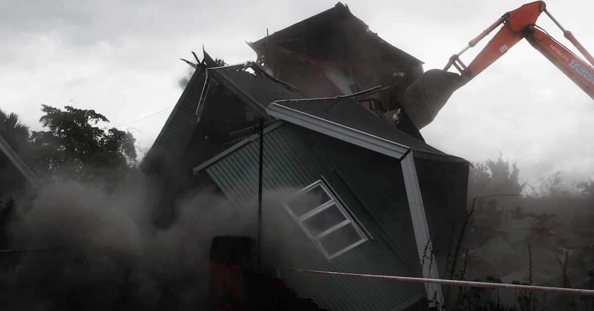 A digger demolishes the oldest house on Bealey Avenue on Feb. 26, 2011, in Christchurch, New Zealand.</p>