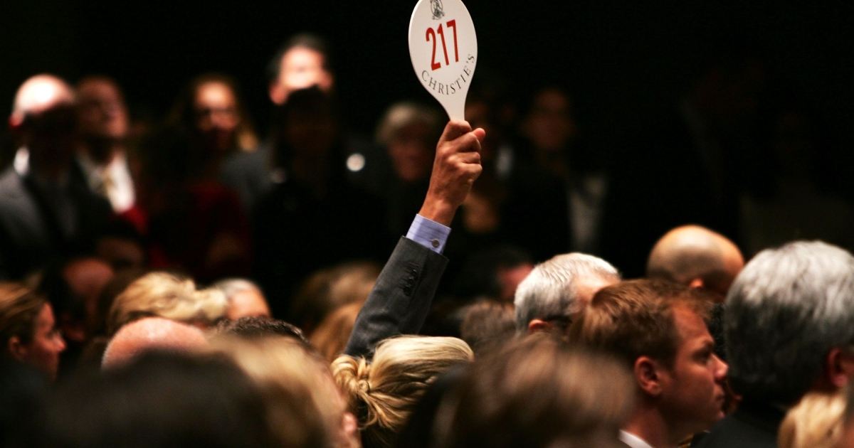A man holds his hand up while bidding on a work of art inside the Christie's auction house in New York City in 2006.</p>