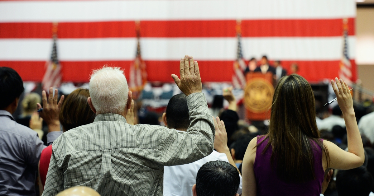 US citizenship candidates take the oath during a naturalization ceremony at the Los Angeles Convention Center on June 27, 2012.</p>