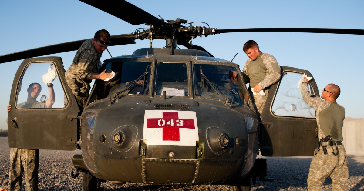 Staff Sgt. Stephon Flynn, Chief Warrant Officer 2 Matt Grove, Spc. Josh Diehl and Chief Warrant Officer 2 Greg Love polish the windows of their medevac helicopter at Forward Operating Base Pasab in Zhari July 2.</p>