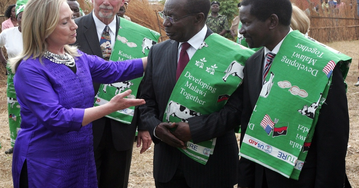 US Secretary of State Hillary Clinton talks to Malawian Minister of Agriculture Peter Mwanza (C) and Malawian Foreign Minister Ephraim Mganda Chiume (L) at the Lumbadzi Milk Bulking Group on August 5, 2012 in Lilongwe, Malawi.</p>