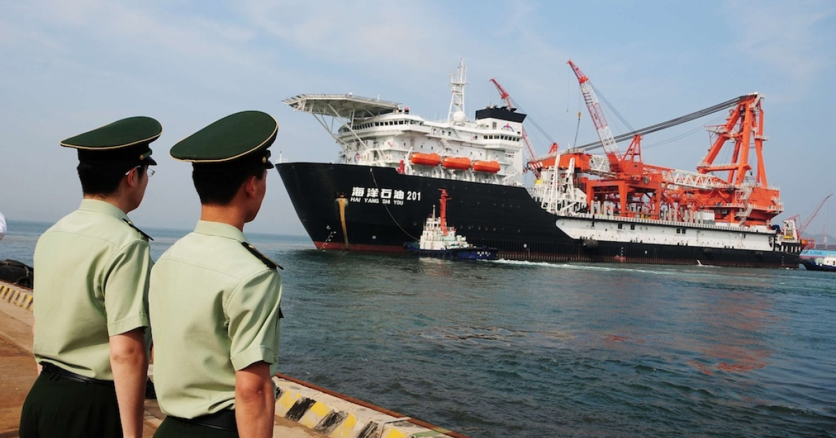 Two Chinese paramilitary guards watch as CNOOC's first independent deep-water oil drilling rig leaves the port of Qingdao, in the eastern province of Shandong, on May 21, 2012.</p>