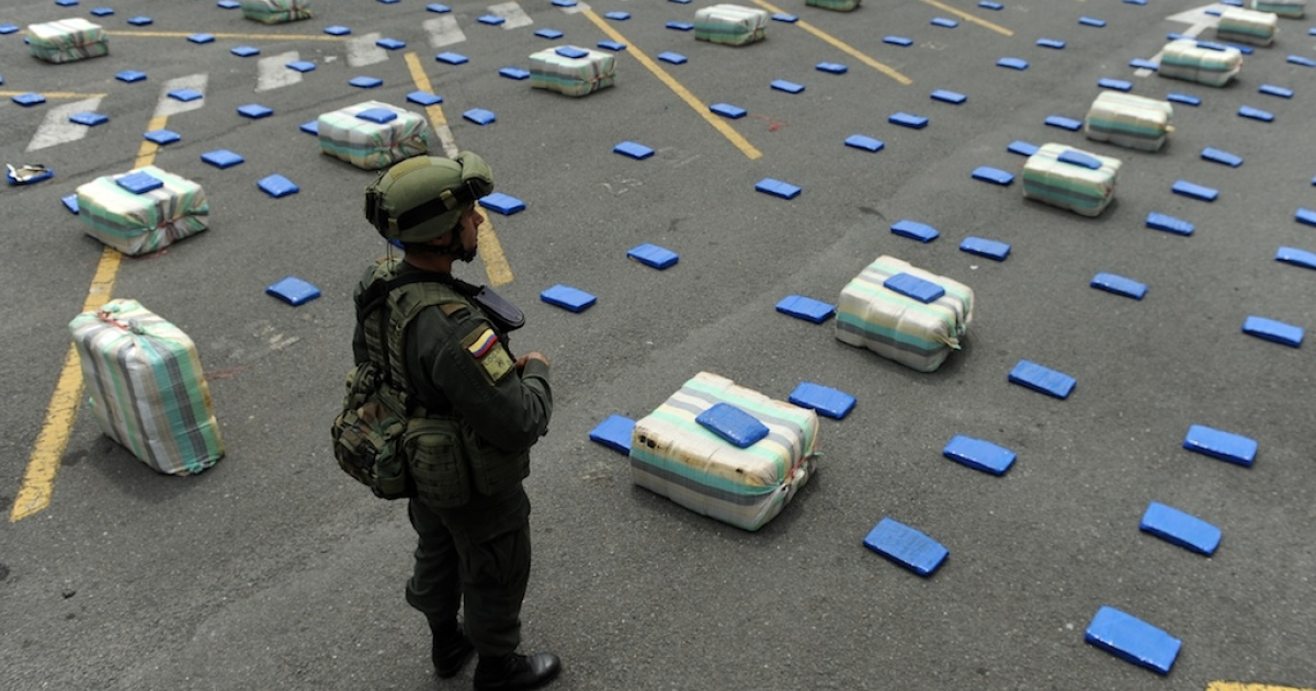 A Colombian anti-drugs police officer stands guard next to marijuana packages on June 26, 2012, in Cali, department of Valle del Cauca, Colombia.</p>