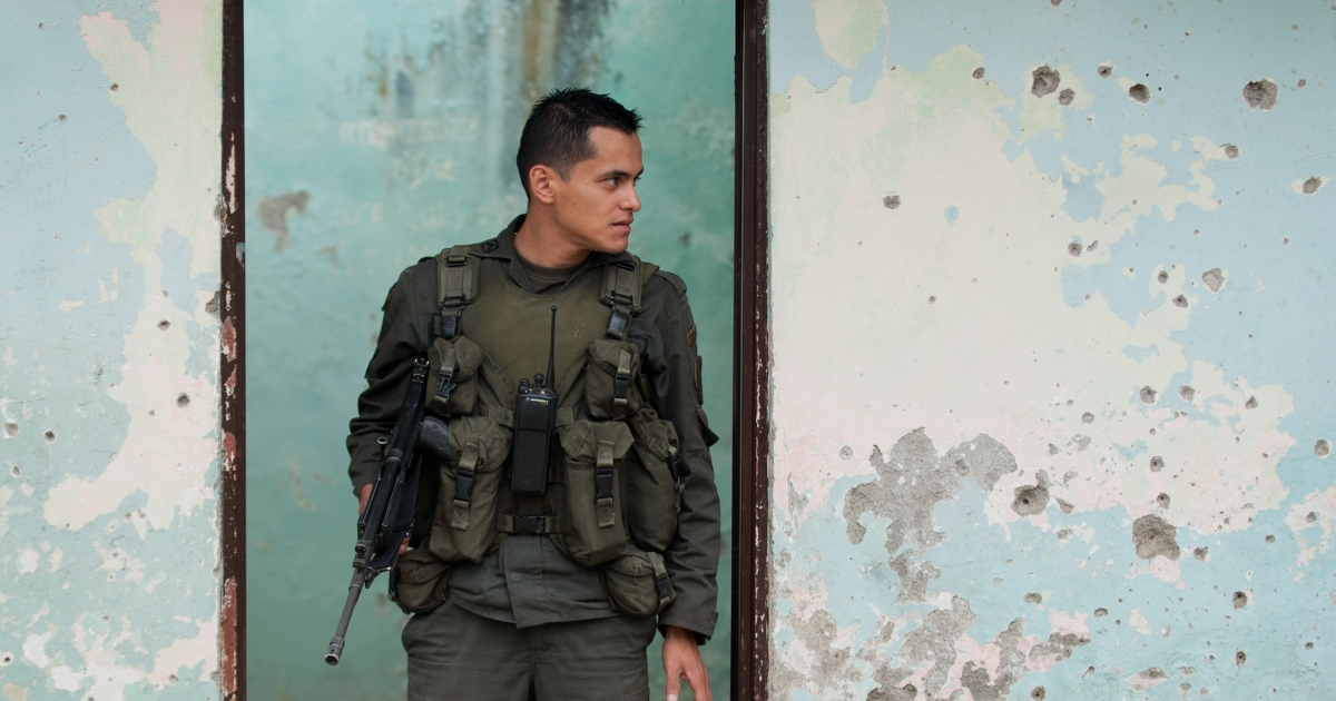 A Colombian policeman guards a building full of bullet holes in the Colombian department of Cauca, where tensions have been mounting among Colombian security forces, the local indigenous population and the leftist guerrilla group the Revolutionary Armed Forces of Colombia, or FARC.</p>