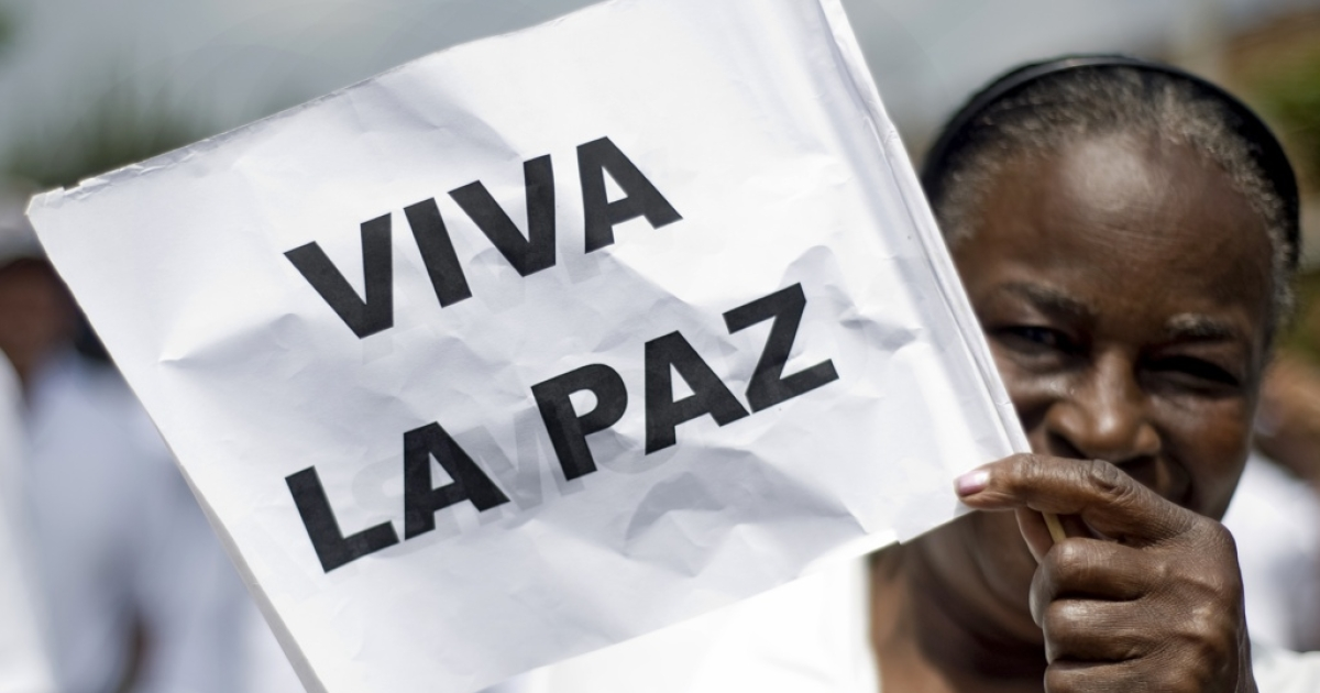 A Colombian woman holds up a flag that reads