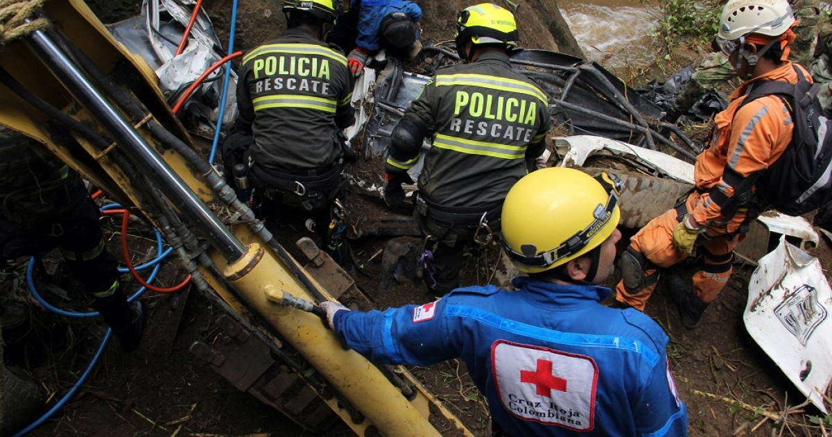 Soldiers, policemen and Red Cross members search for victims on December 30, 2012, after a landslide along a road between the cities of Neiva and Florencia, in southwestern Colombia.</p>
