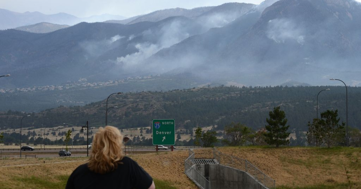 A local resident watches smoke from the Waldo Canyon fire, June 28, 2012 near the Air Force Academy in Colorado Springs, Colorado.</p>