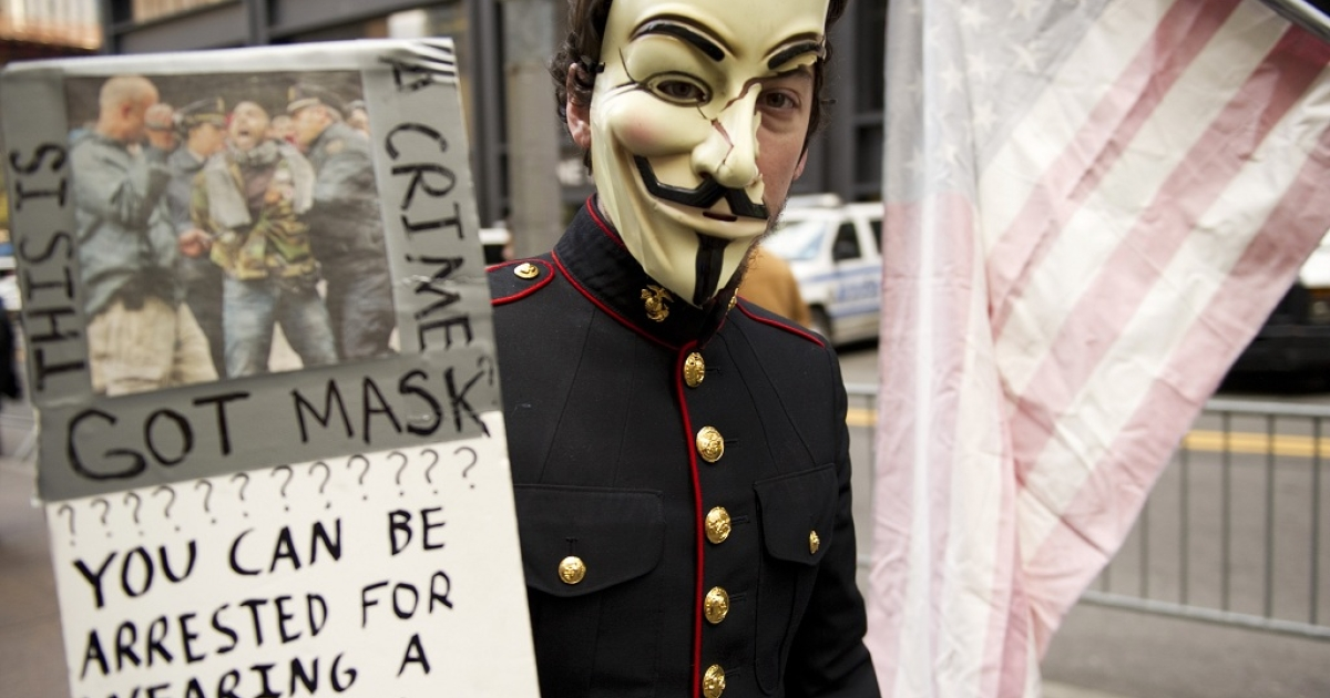 A young man with an Anonymous mask, wearing a military uniform, marches with Occupy Wall Street protesters on November 11, 2011 at Zuccotti Park in New York.</p>