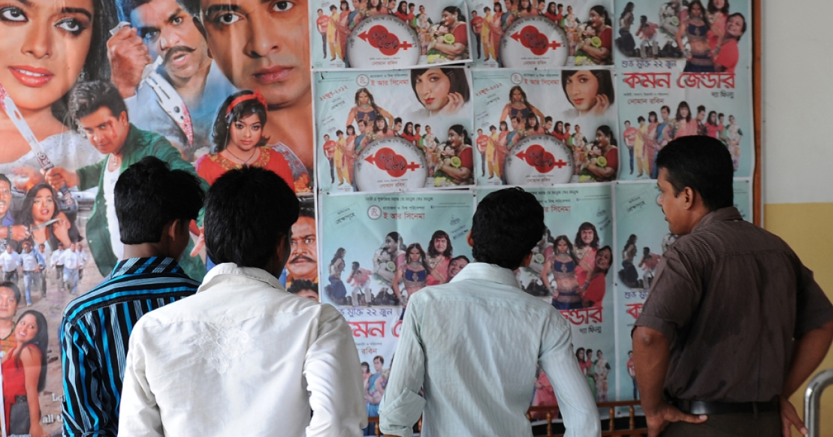 Bangladeshi men look at a poster advertising the film 'Common Gender' at a movie theatre in Dhaka on July 6, 2012. A film about a love affair between a transgender person and a Hindu boy has become a surprise hit in Bangladesh, with distributors saying on July 8 that it would now be given a general release.</p>