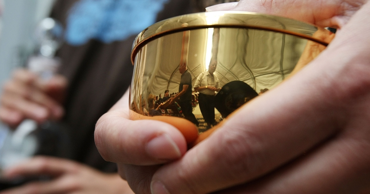 Parishoners are reflected in a Communion chalice during Sunday Mass at Saint Clare Catholic Church's temporary tent sanctuary in Waveland, Miss., on August 19, 2007.</p>