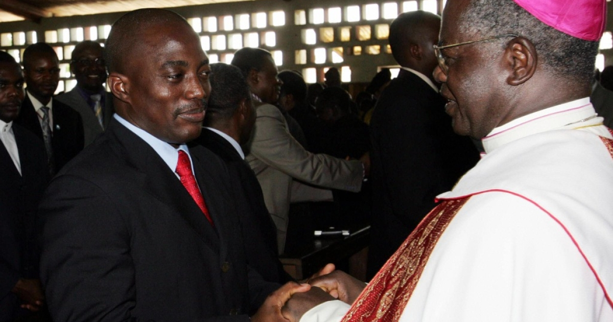 Democratic Republic of Congo (DRC) President Joseph Kabila (L) shakes hands with Catholic Archbishop Laurent Monsengwo (R) at the end of an ecumenical ceremony, 17 October 2004 in KIsangani during his landmark visit to the troubled east of the vast central African country. The two-hour service was held at Saint Joseph's Church in Kisangani's Tchopo district, which was especially hard hit during the DRC's 1998-2003 war.</p>