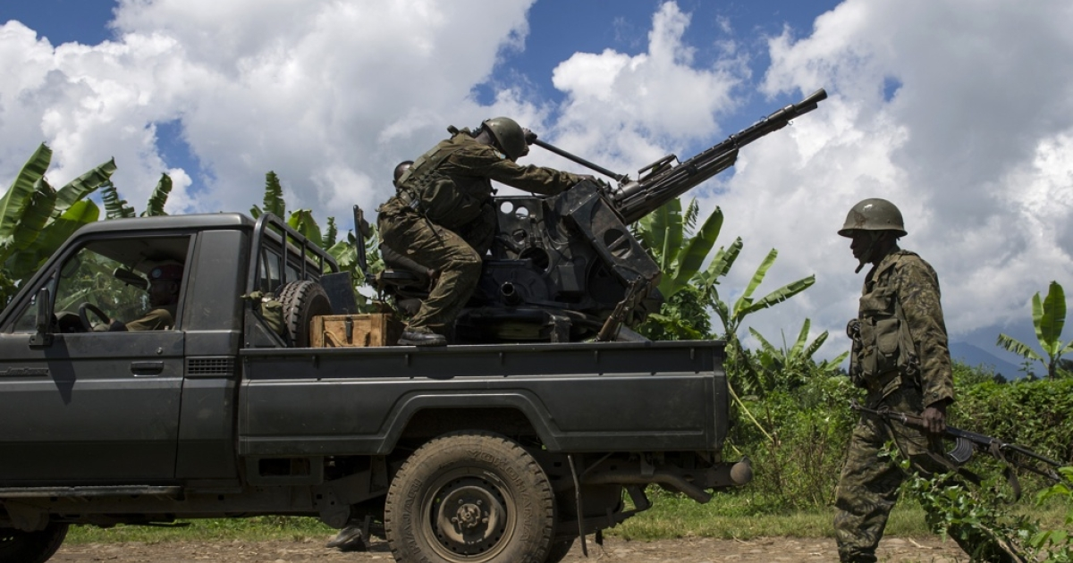 A soldier of the Armed Forces of the Democratic Republic of the Congo (FARDC) walks past a truck-mounted machine gun in the bush of Jomba in restive North Kivu province on May 19, 2012. The Congolese army was engaged in an intense firefight with M23 rebels in the hills above the village of Kinyamahura, near  Bunagana, on the border with Uganda.</p>