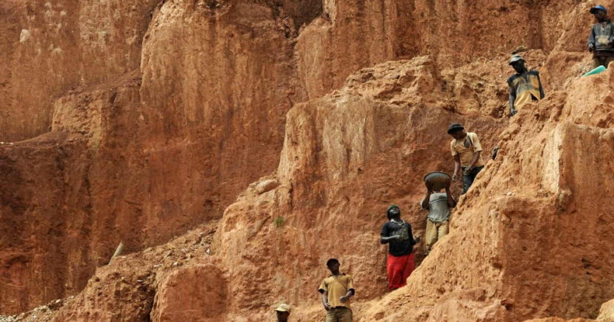 Workers stand on a muddy cliff as they work at a gold mine on Feb. 23, 2009 in northeastern Congo.</p>
