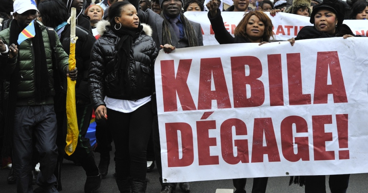 Katumba's death places Congo at a more dangerous point even than last year's elections. Here, DR Congo demonstrators shout, holding a banner that reads,