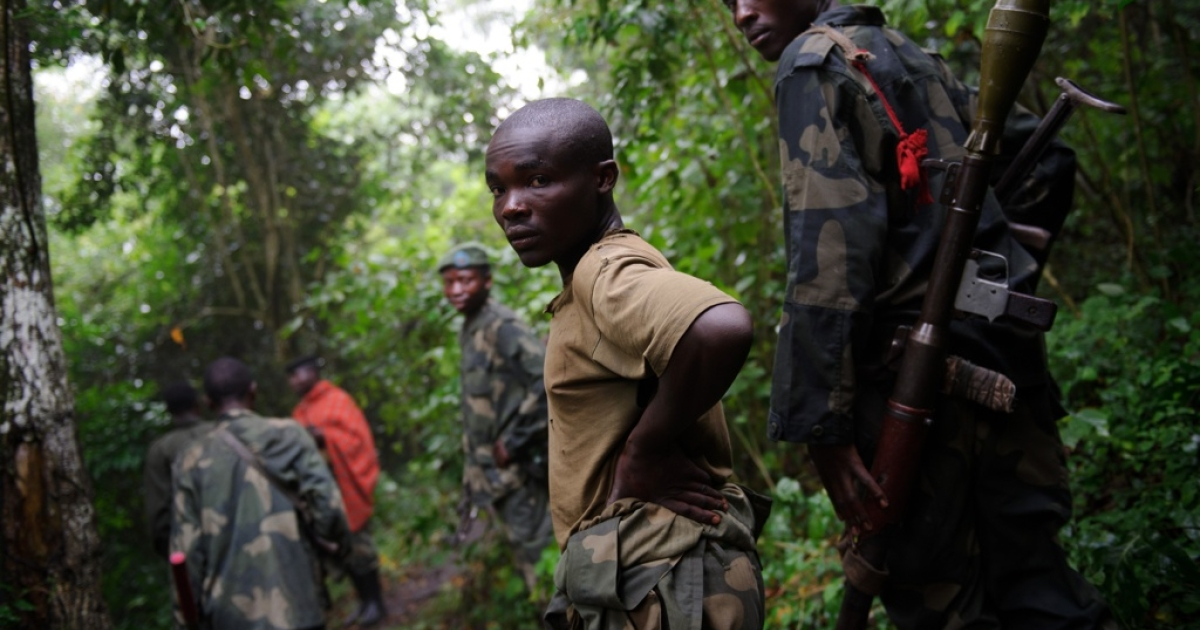 M23 rebels walk through the jungle in the Democratic Republic of the Congo's restive North Kivu province on July 28, 2012.</p>