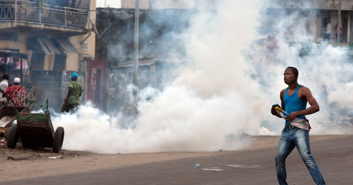 A supporter of opposition leader Etienne Tshisekedi  stands next to tear gas fired by police to disperse demonstrators in Kinshasa on December 23, 2011. DR Congo police banned a swearing-in ceremony that day for opposition leader Etienne Tshisekedi, who held the event in his house after soldiers blocked the entrance to the stadium.</p>