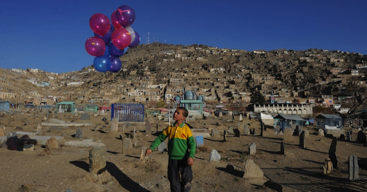 Afghan child Abdul Wahid, 10, waits for customers as he sells balloons at a cemetery in Kabul on Nov. 30, 2011. A 13-year-old boy from Herat Province was recently sentenced to a year in prison for having sex with two adult men, in a case that's drawn the ire of human rights groups.</p>