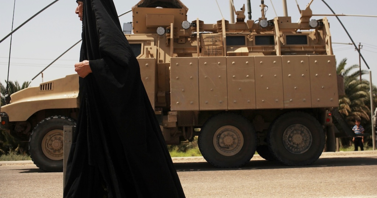 #175 — Iraq<br />An Iraqi woman walks by a US military vehicle belonging to the 3rd Armored Cavalry Regiment while on patrol on July 16, 2011, in Iskandariya, Iraq.</p>