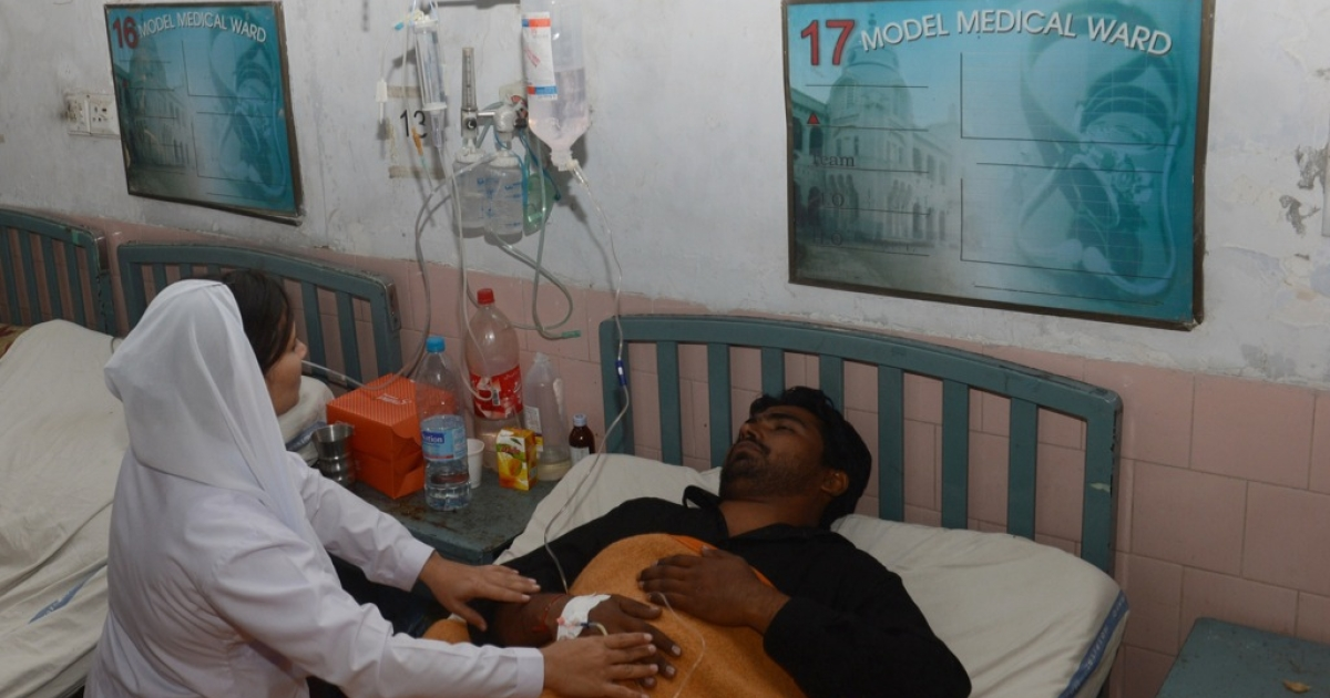 A Pakistani paramedic staff gives medical treatment to a patient who fell ill after drinking a toxic cough syrup at a hospital in Lahore on November 26, 2012. At least 16 people have died after drinking a toxic cough syrup in the Pakistani city of Lahore, forcing authorities to close three pharmacies and a medicine factory, officials said.</p>