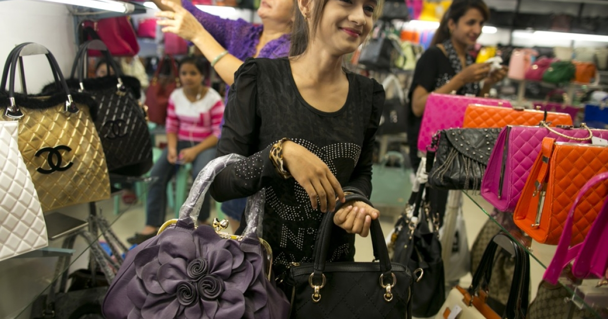 A Burmese woman holds counterfeit Chinese made luxury brand ladies bags at an outdoor market in the Golden Triangle, situated along the Thai- Burma border on November 12, 2012 in Tachiliek, Myanmar.</p>