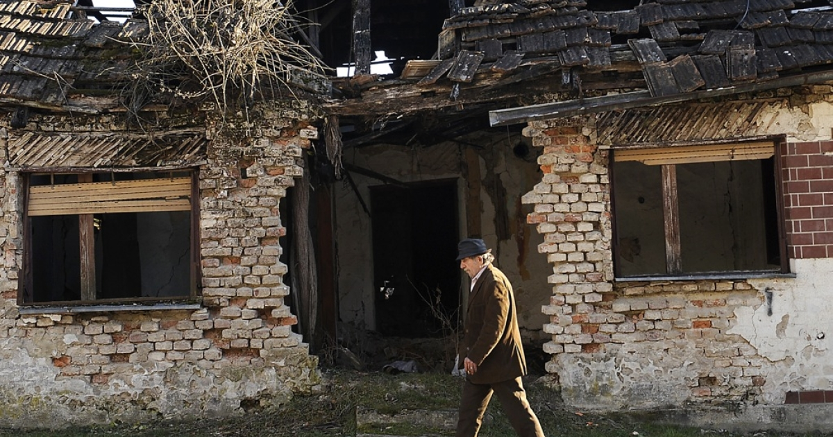 A man passes by the ruins of the 1991-1995 Serbo-Croatian war in the central Croatian town of Dvor, some 150 kilometers from capital Zagreb on Jan. 18, 2012. Croatian Serbs, whose rights were among key criteria for Zagreb's EU bid, hope that its entry in the bloc, on which the country votes in a referendum on Jan. 21, could further affirm their minority.</p>
