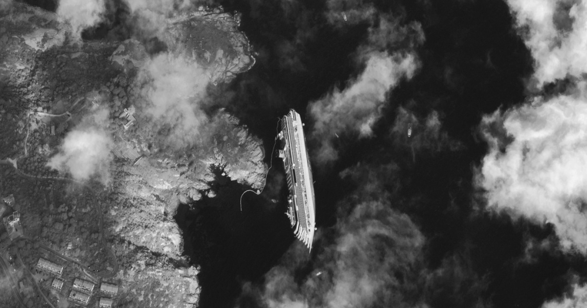 View of the stricken Costa Concordia cruise ship on January 17, 2012, after it capsized near Giglio, Italy. Photo by DigitalGlobe.</p>