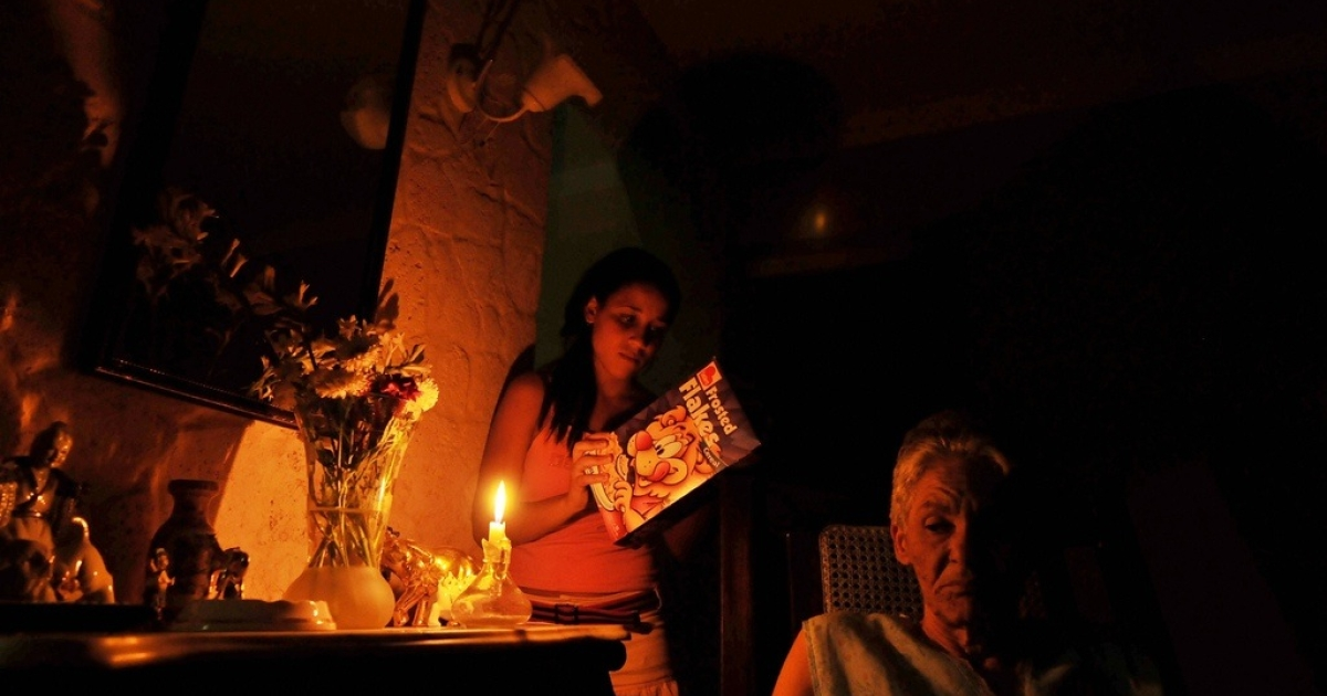 A Cuban girl reads the inscriptions on a food box by candlelight during a power cut on May 31, 2009.</p>