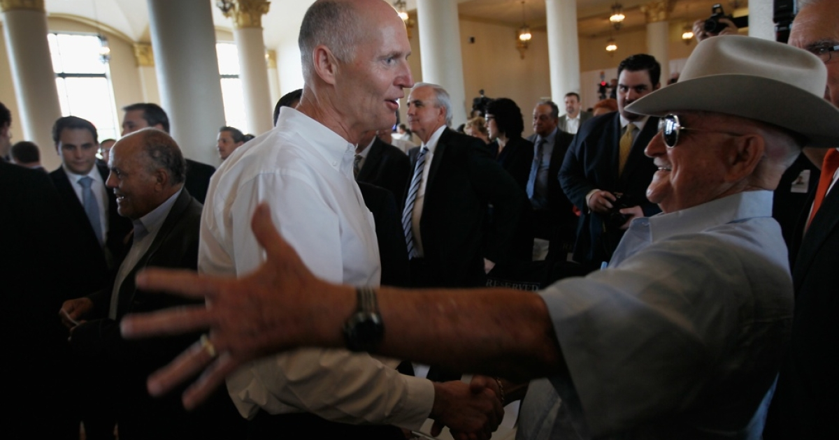Florida Gov. Rick Scott, left, greets a supporter before signing a bill that bans business with companies tied to Cuba or Syria, on May 1 in Miami.</p>