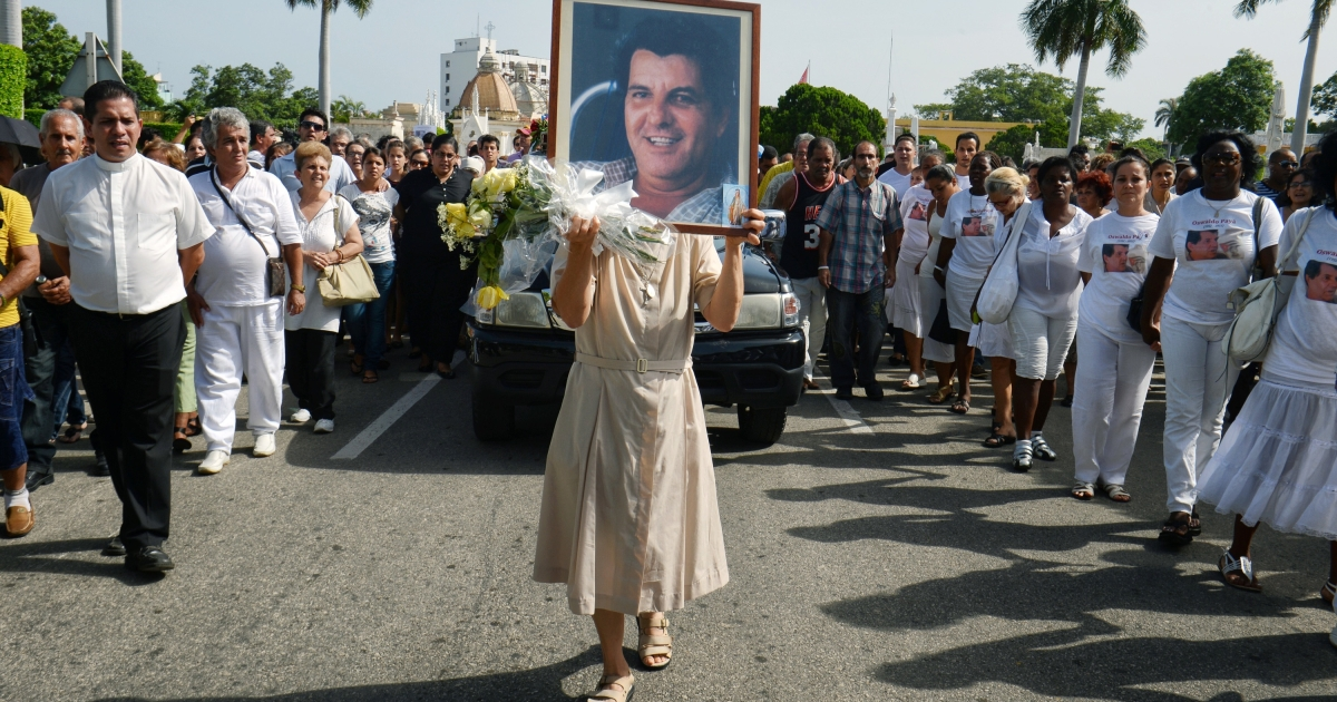 A nun holds a portrait of Cuban opposition leader Oswaldo Paya during his funeral ceremony, on July 24, 2012 at Cristobal Colon cemetery in Havana.</p>