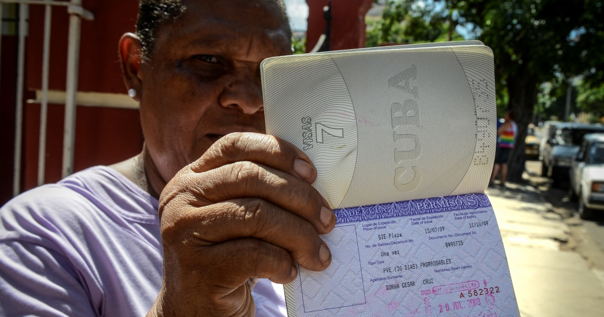 Cuban Cruz Duran shows her passport with a travel permission.</p>