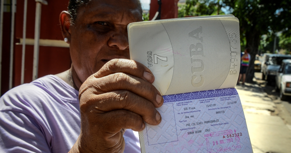 Cuban Cruz Duran shows her passport with a travel permission on Oct. 16 in Havana. More Cubans could soon be like Duran after the government lifts the exit permit required to travel.</p>