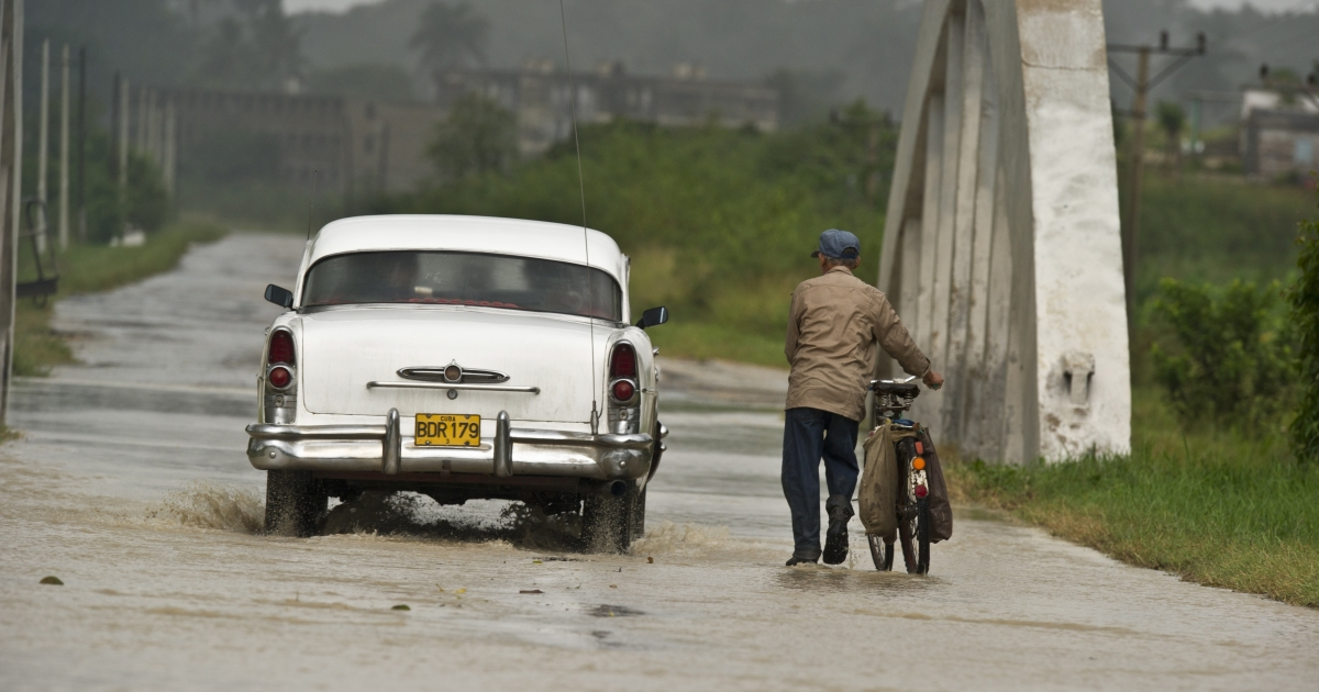 A farmer with his bicycle and a car wade a flooded road, on Oct. 14, 2010, in the municipality of Bahia Honda, 90 km west of Havana, Pinar del Rio province, Cuba, as tropical storm Paula approaches.</p>