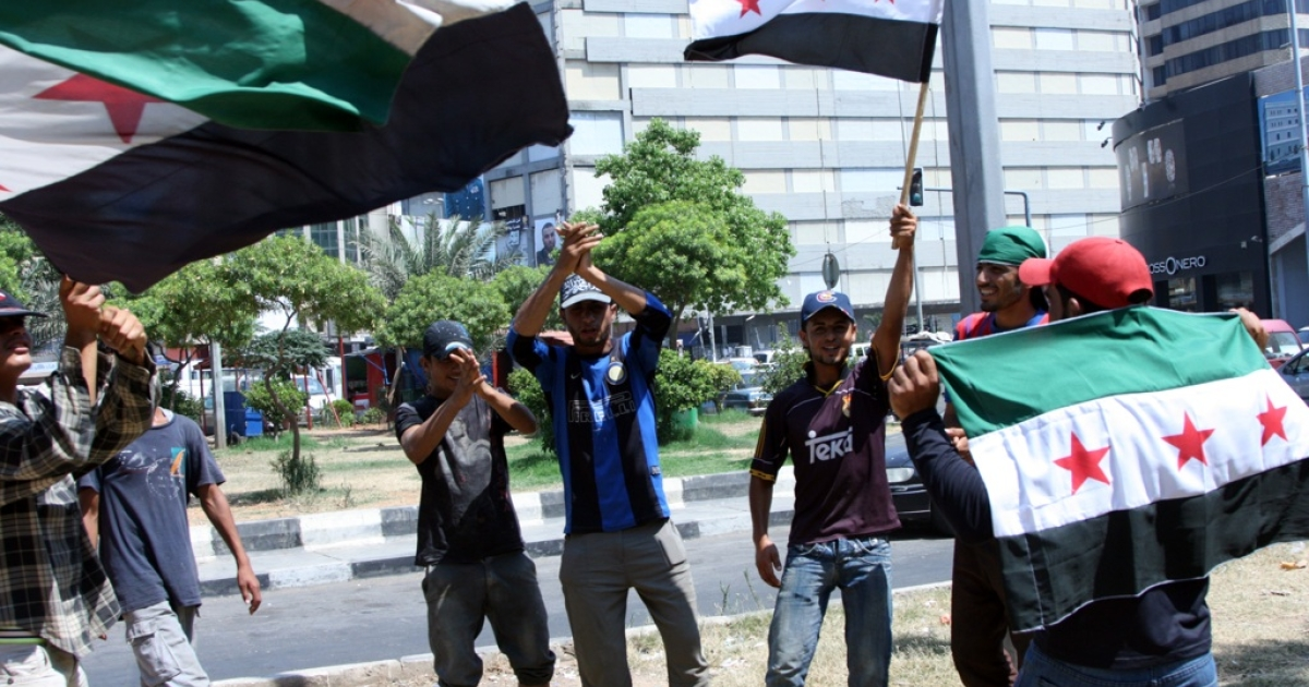 Lebanese men wave pre-Baath flags, that were adopted by the Syrian revolution during the uprising, as they celebrate in the centee of Lebanon's northern town of Tripoli on July 18, 2012, the death of Syrian defense minister General Daoud Rajha in a suicide attack targeting the National Security headquarters in central Damascus.</p>