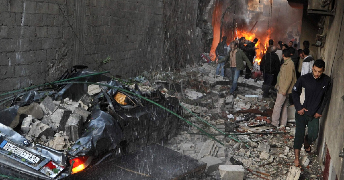 Syrian men inspect the scene of a car bomb explosion in Jaramana, a mainly Christian and Druze suburb of Damascus, on November 28, 2012. At least two car bombs exploded in Damascus killing and injuring a number of people.</p>