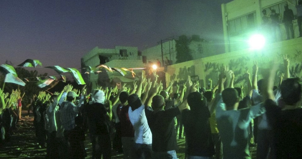 Demonstrators raise their arms as Syrian opposition flags are seen during a protest against Syria's President Bashar al-Assad in Damascus July 16, 2012.</p>