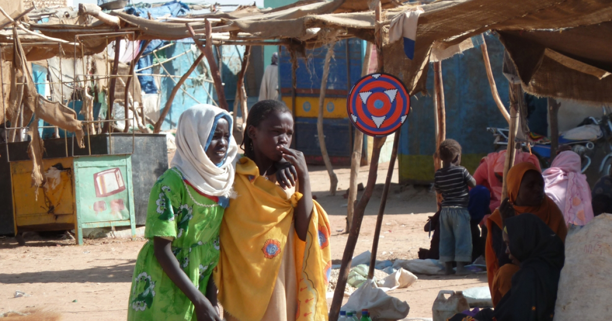 Two girls walk through the market in the Abushouk Internally Displaced Persons (IDP) camp, home to nearly 55,000 people, near the North Darfur capital El Fasher. Nearly a decade after government-backed Janjaweed militias began a