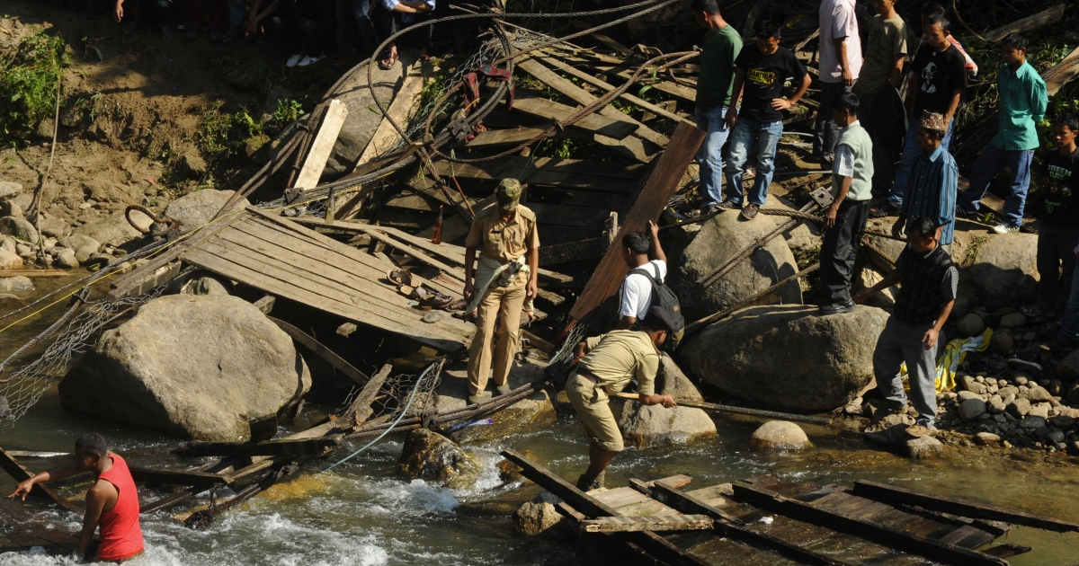 Indian villagers and rescuers gather at the scene of a bridge that collapsed the night before in the village of Bijonbari in West Bengal's Darjeeling district on October 23, 2011.</p>